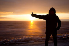 Homme sur la roche sur la mer dans la glace - silhouette Photographie stock libre de droits