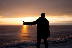 Homme sur la roche sur la mer dans la glace - silhouette Images stock