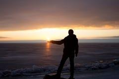 Homme sur la roche sur la mer dans la glace - silhouette Photos stock