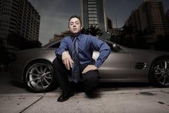 Homme sur la rue avec sa voiture de sport de luxe photo stock