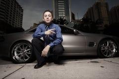 Homme sur la rue avec sa voiture de sport de luxe Photographie stock libre de droits