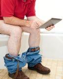 Homme sur la toilette avec le PC de tablette Image libre de droits