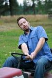 Homme sur la tondeuse à gazon Photographie stock libre de droits