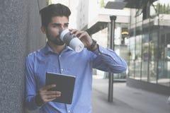 Homme sur le café de rue de ville et iPod potables de se tenir Station thermale photos stock