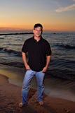 Homme sur le coucher du soleil de plage photo stock