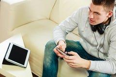 Homme sur le divan avec des écouteurs smartphone et comprimé image libre de droits