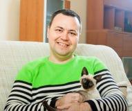 Homme sur le divan   avec l'animal familier images stock