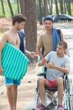 Homme sur le fauteuil roulant et les amis sur la plage Images libres de droits