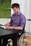 Homme sur le fauteuil roulant lisant un livre Photographie stock libre de droits