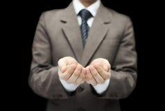 Homme sur le fond noir avec les mains ouvertes Photo stock