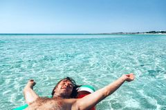 Homme sur le lilo sur la plage Image stock