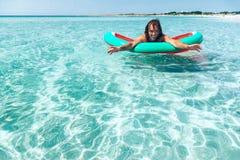 Homme sur le lilo sur la plage Image libre de droits