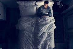 Homme sur le lit utilisant son comprimé image libre de droits
