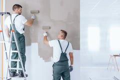 Homme sur le mur de peinture d'échelle Images stock
