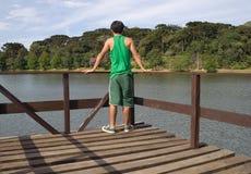 Homme sur le pilier par le lac scénique Image stock