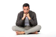 Homme sur le plancher avec des mains sous le menton Photographie stock libre de droits
