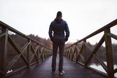 Homme sur le pont en bois au-dessus d'un lac, un jour humide d'automne Image libre de droits