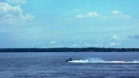 Homme sur le scooter de mer fonctionnant sur l'eau banque de vidéos