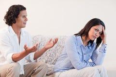 Homme sur le sofa essayant de faire des excuses à son amie Photographie stock