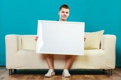 Homme sur le sofa tenant le conseil de présentation vide photographie stock libre de droits