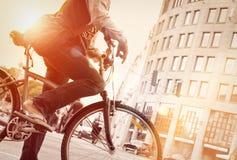 Homme sur le vélo dans le trafic avec le sunflare Photos libres de droits