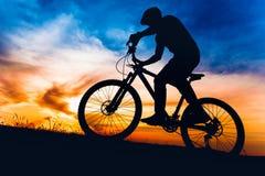 Homme sur le vélo de montagne au coucher du soleil, bicyclette de monte sur des collines photo stock