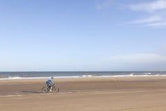 Homme sur le vélo de montagne sur la plage avec le ciel bleu Photo libre de droits