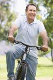 Homme sur le vélo souriant à l'extérieur Photos stock