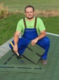 Homme sur les bardeaux de bitume d'attache de toit sur le bâtiment d'annexe Image libre de droits