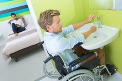 Homme sur les mains de lavage de fauteuil roulant dans la salle de bains photos libres de droits