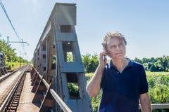 Homme sur les voies ferrées proches mobiles photos libres de droits