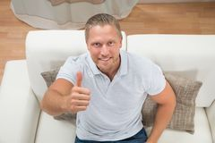 Homme sur Sofa Showing Thumbs Up Photos stock