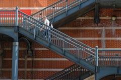 Homme sur un escalier métallique devant un mur de briques Photo libre de droits