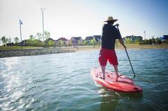 Homme sur un panneau de palette sur le lac Images libres de droits