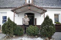 Homme sur un porche de la maison blanche de village avec les buissons verts en avant Images libres de droits
