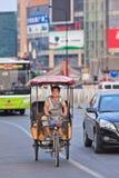 Homme sur un pousse-pousse motorisé électrique, Pékin, Chine Photos stock