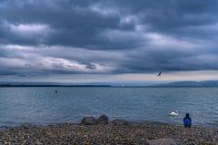 Homme sur un rivage de lac sous le ciel orageux Photographie stock