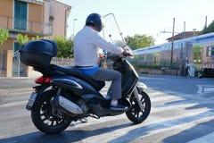 Homme sur un scooter attendant passant le train de voyageurs photographie stock libre de droits