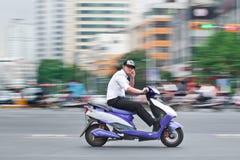 Homme sur un vélo électrique au centre de la ville de Kunming, Chine Photos stock