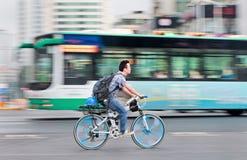 Homme sur un vélo de montagne de Lamborghini avec l'autobus sur le fond, Kunming, Chine Image libre de droits