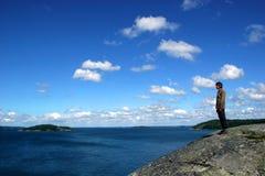Homme sur une île observant la mer baltique, Finlande photo stock