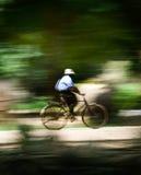 Homme sur une bicyclette (tache floue de mouvement à la vitesse de portrait) Image stock