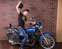 Homme sur une motocyclette soulevant son casque noir Photo libre de droits