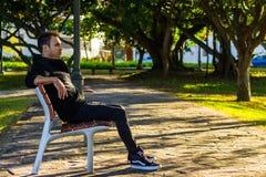 Homme sur une pensée de banc de parc Photographie stock libre de droits