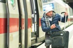 Homme tapi et sa valise à la station photo stock