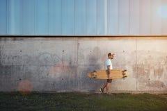 Homme tatoué avec le longboard à côté d'un mur en béton Image stock