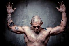 Homme tatoué musculaire avec des mains augmentées vers le haut Photo libre de droits