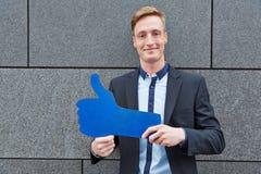 Homme tenant de grands pouces bleus  Photographie stock