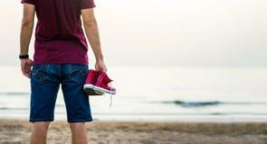 Homme tenant des espadrilles sur la plage Photographie stock