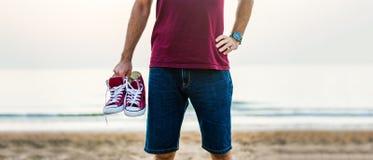 Homme tenant des espadrilles sur la plage Image libre de droits